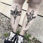 Matching dragonfly tattoos on both shins