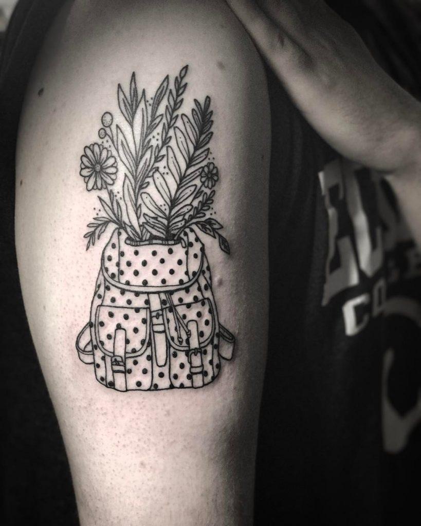 Polka dot backpack and plants tattoo
