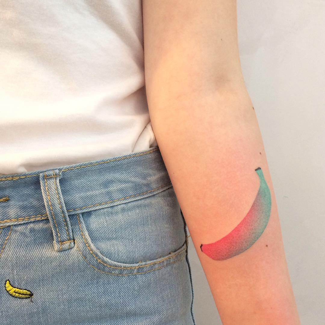 Red and teal banana tattoo