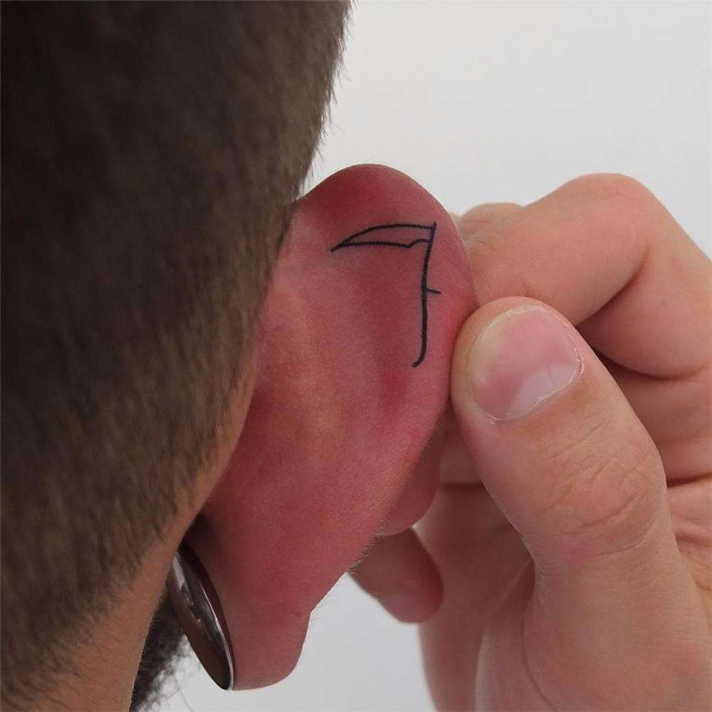 Scythe tattoo on the ear