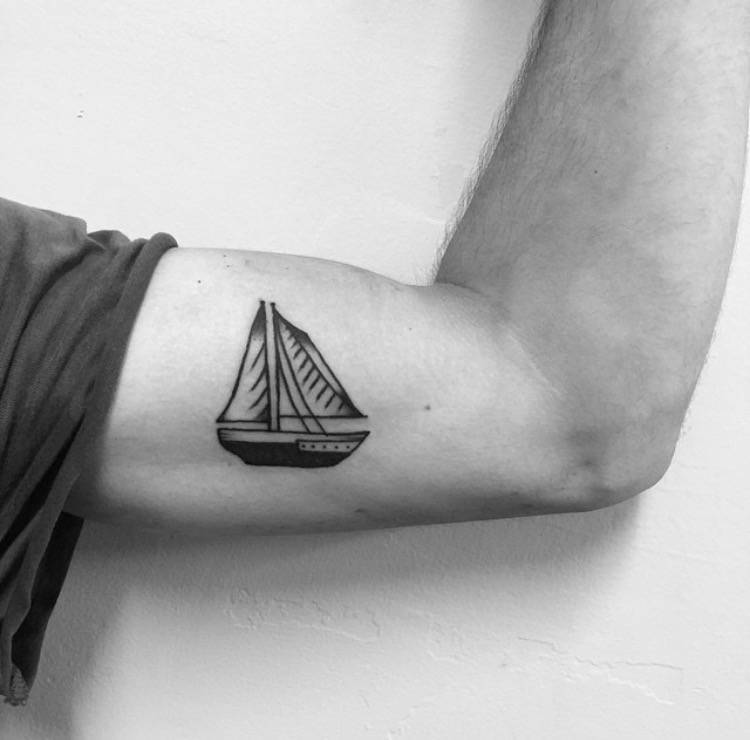 Small boat tattoo on the bicep