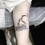 Small sailing boat tattoo on the arm