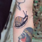 Snail tattoo on the left arm