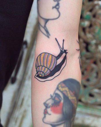 Snail tattoo on the left arm