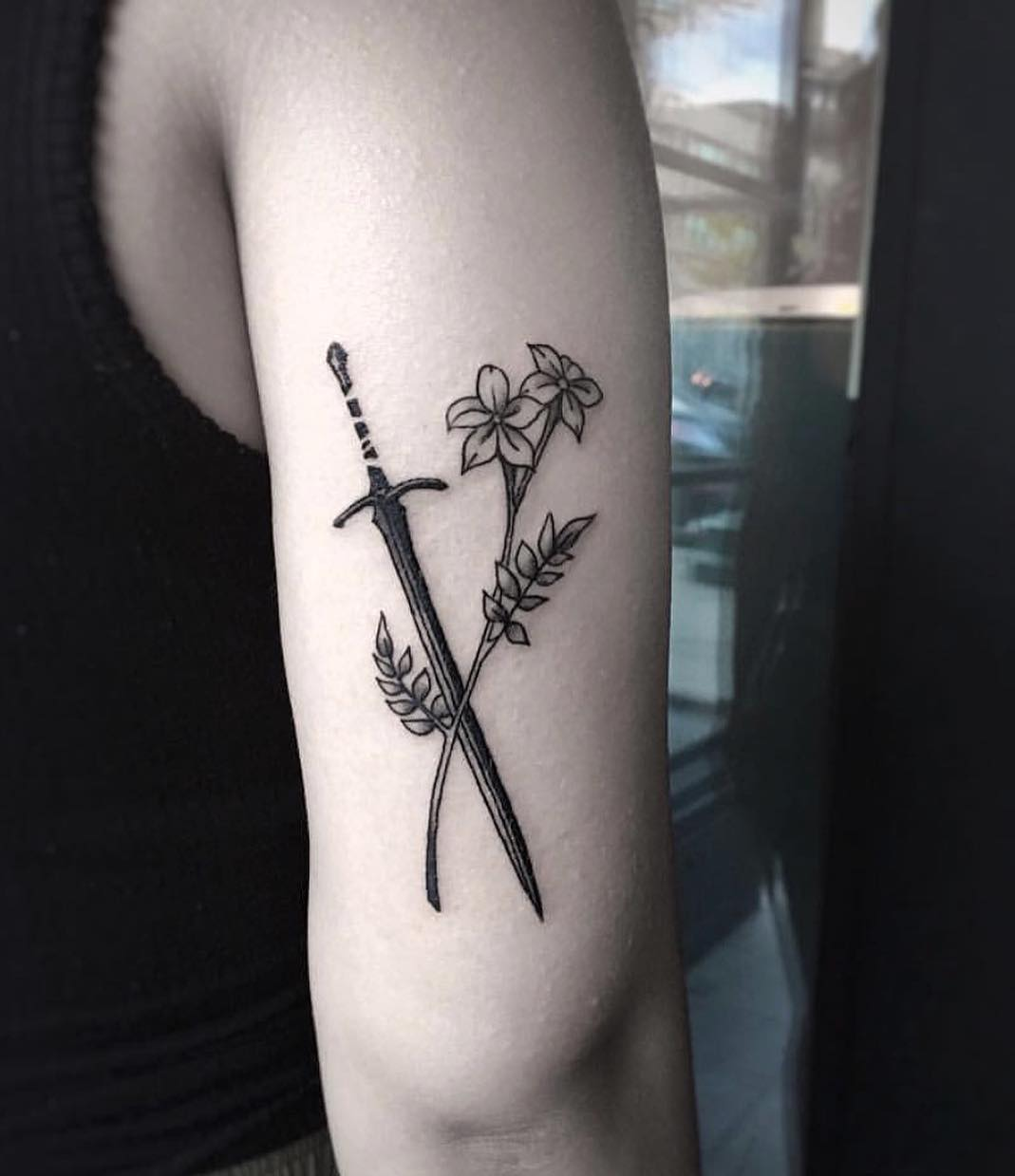 Sword and flower tattoo on the arm