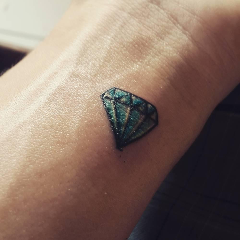 Tiny blue diamond tattoo on the wrist