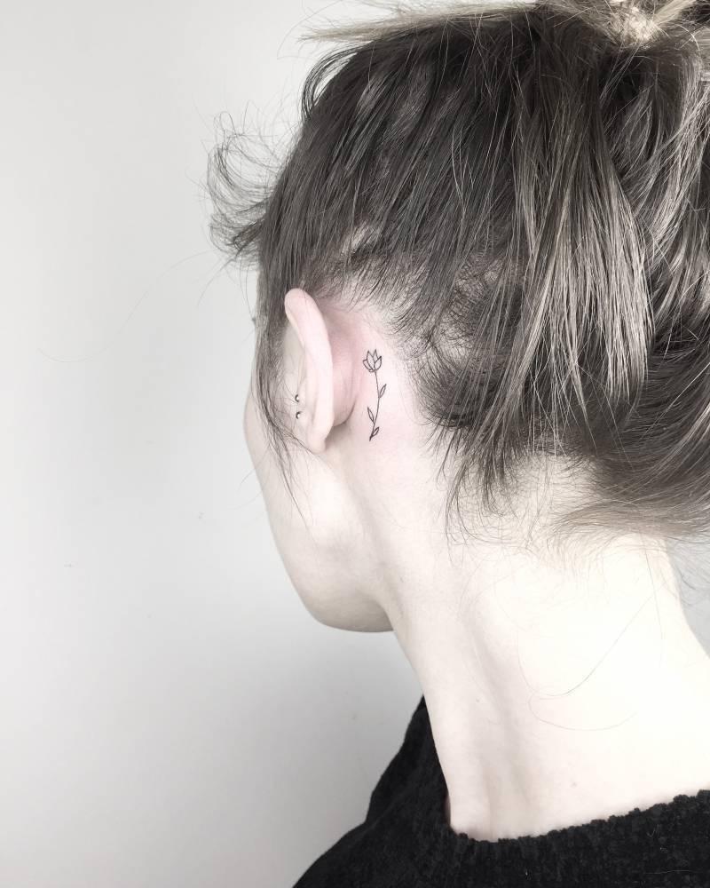 Tiny tulip tattoo behind the left ear