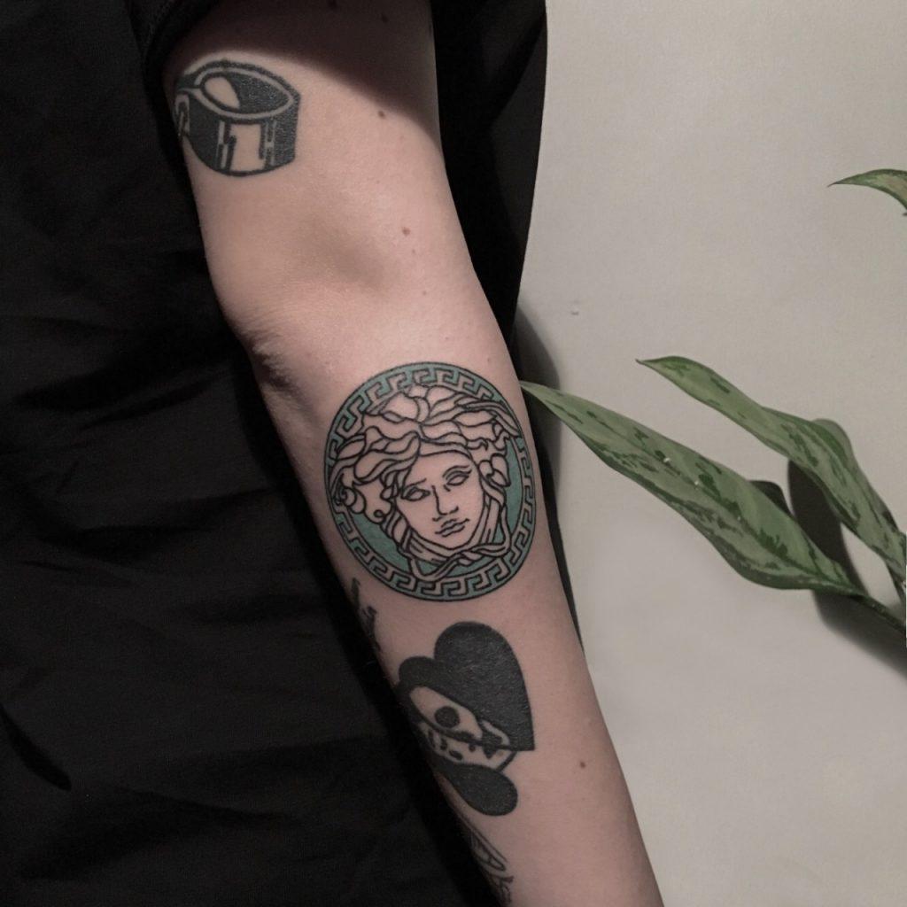 Versace logo tattoo by artist berkin dönmez
