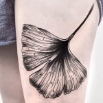 Black ginkgo leaf tattoo on the thigh