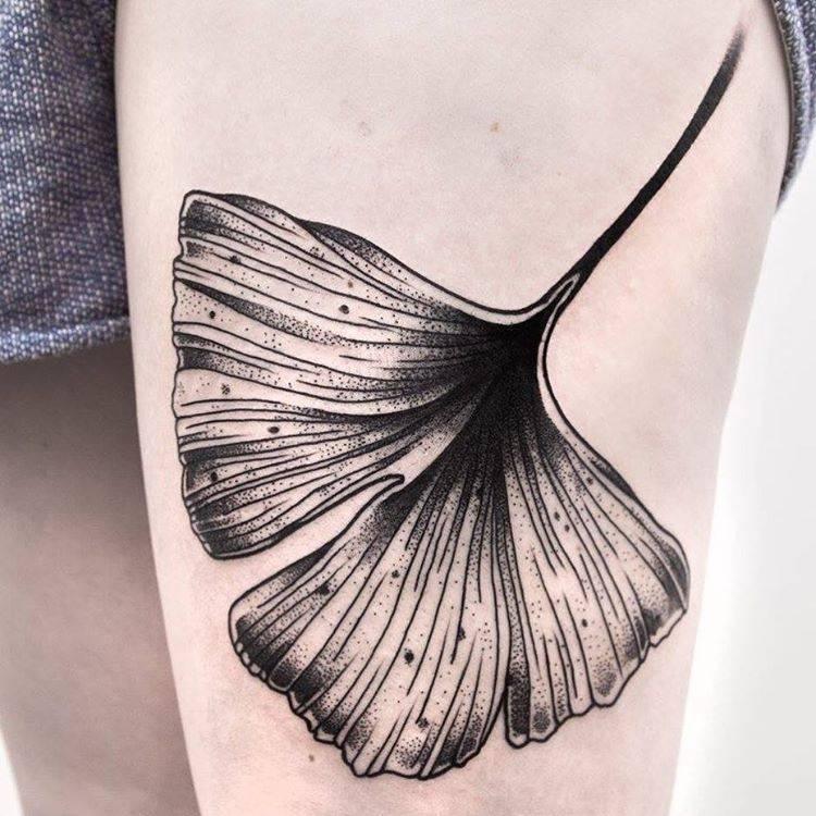 Black ginkgo leaf tattoo on the thigh