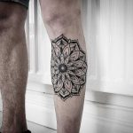 Black mandala tattoo on the shin