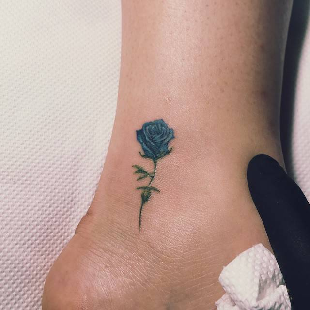 Blue rose tattoo on the outer ankle