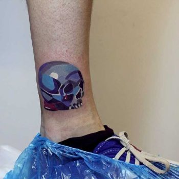 Colorful skull tattoo on the ankle