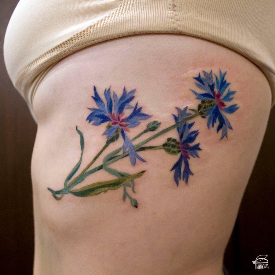 Cornflower tattoo on the rib cage