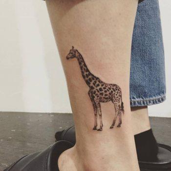Giraffe tattoo on the left calf