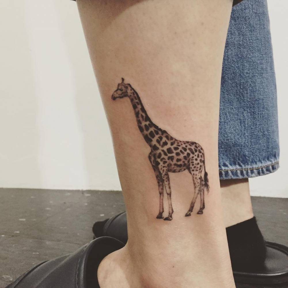 Giraffe tattoo on the left calf