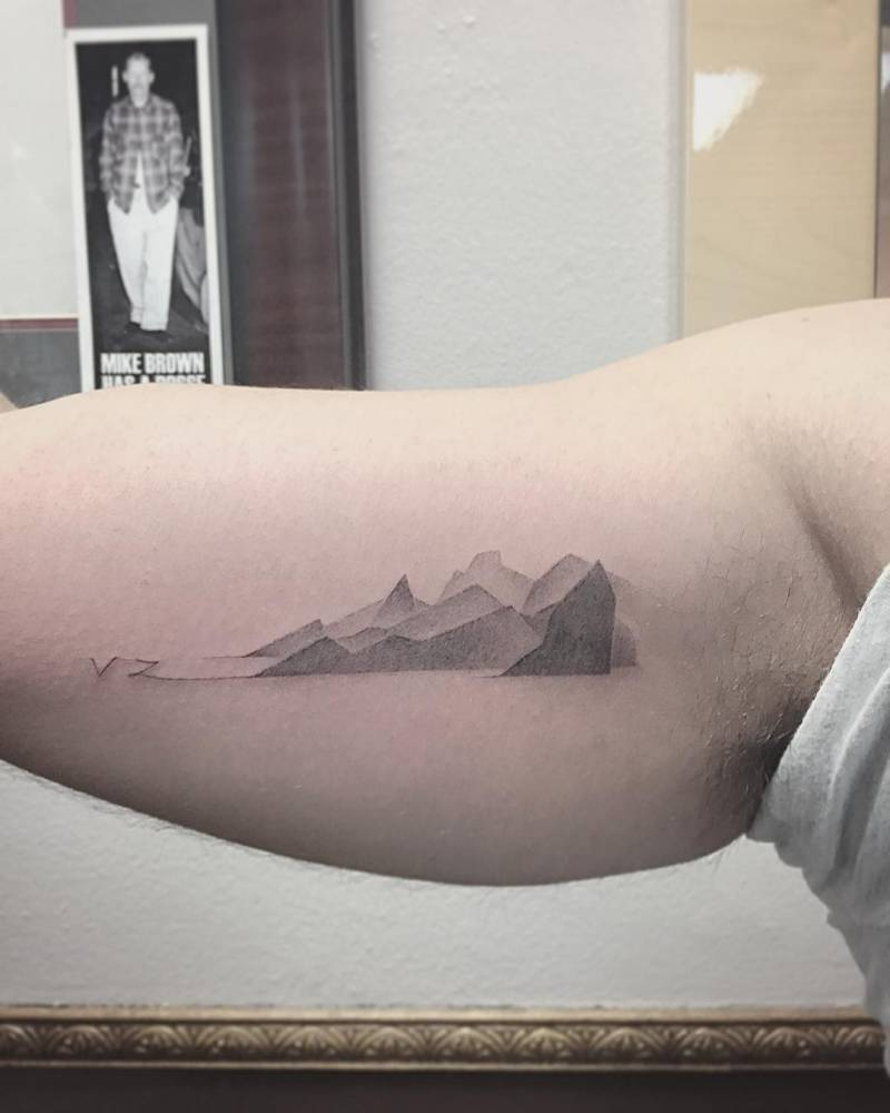 Gradient mountains tattoo on the bicep