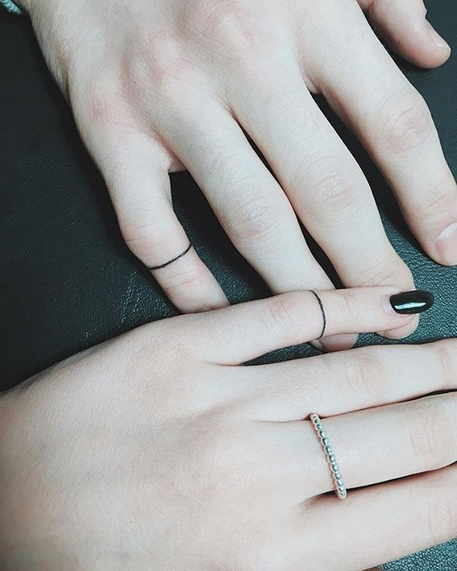 Hand poked matching ring tattoos