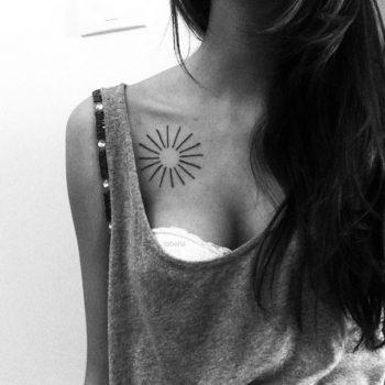 Minimalist sun tattoo on the collarbone