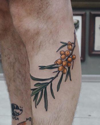 Sea buckthorn tattoo on the calf