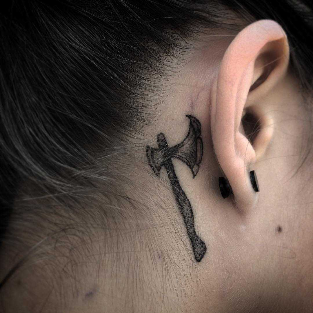 Ax tattoo behind the right ear