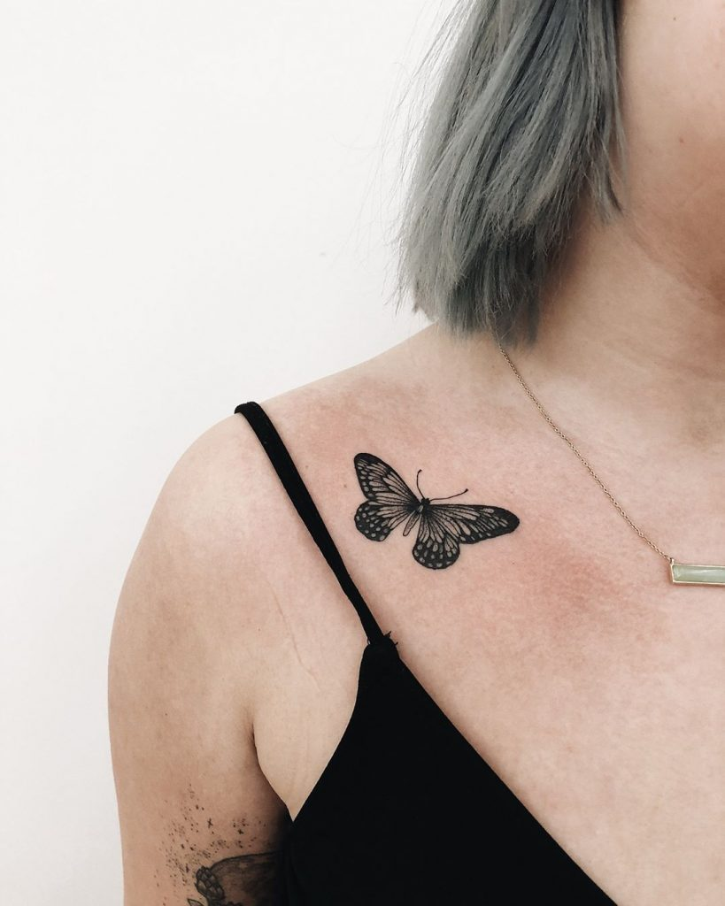 Black small butterfly tattoo on the clavicle bone