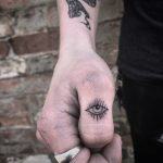 Blackwork eye tattoo on the thumb