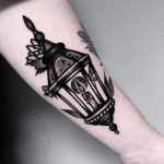 Blackwork lantern tattoo on the forearm