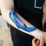 Colorful whale tattoo on the forearm