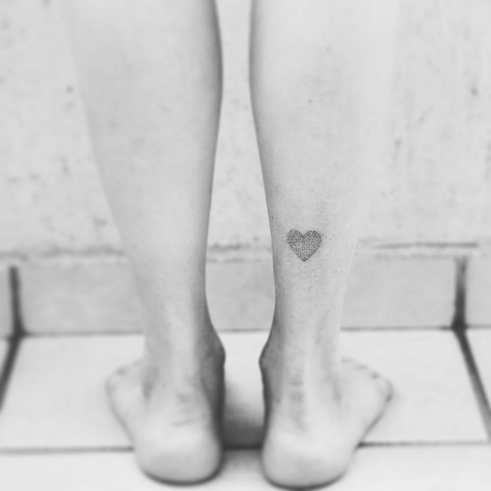 Dot-work style heart tattoo on the right calf