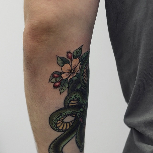 Flowers and snake on the forearm
