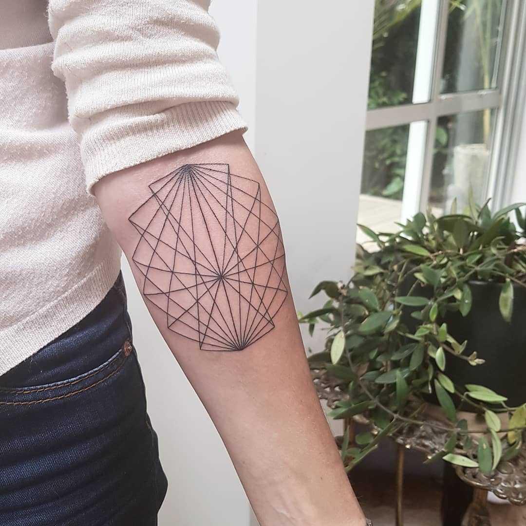 Geometric black tattoo on the left forearm