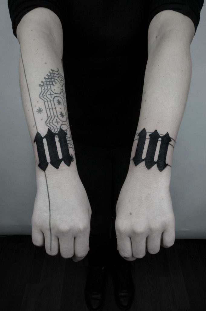 Matching black tattoos on both wrists