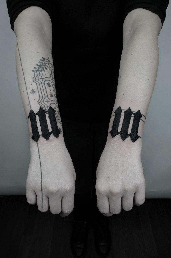 Matching black tattoos on both wrists