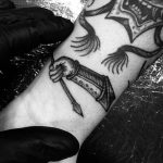 Medieval woodcut style arm and arrow tattoo