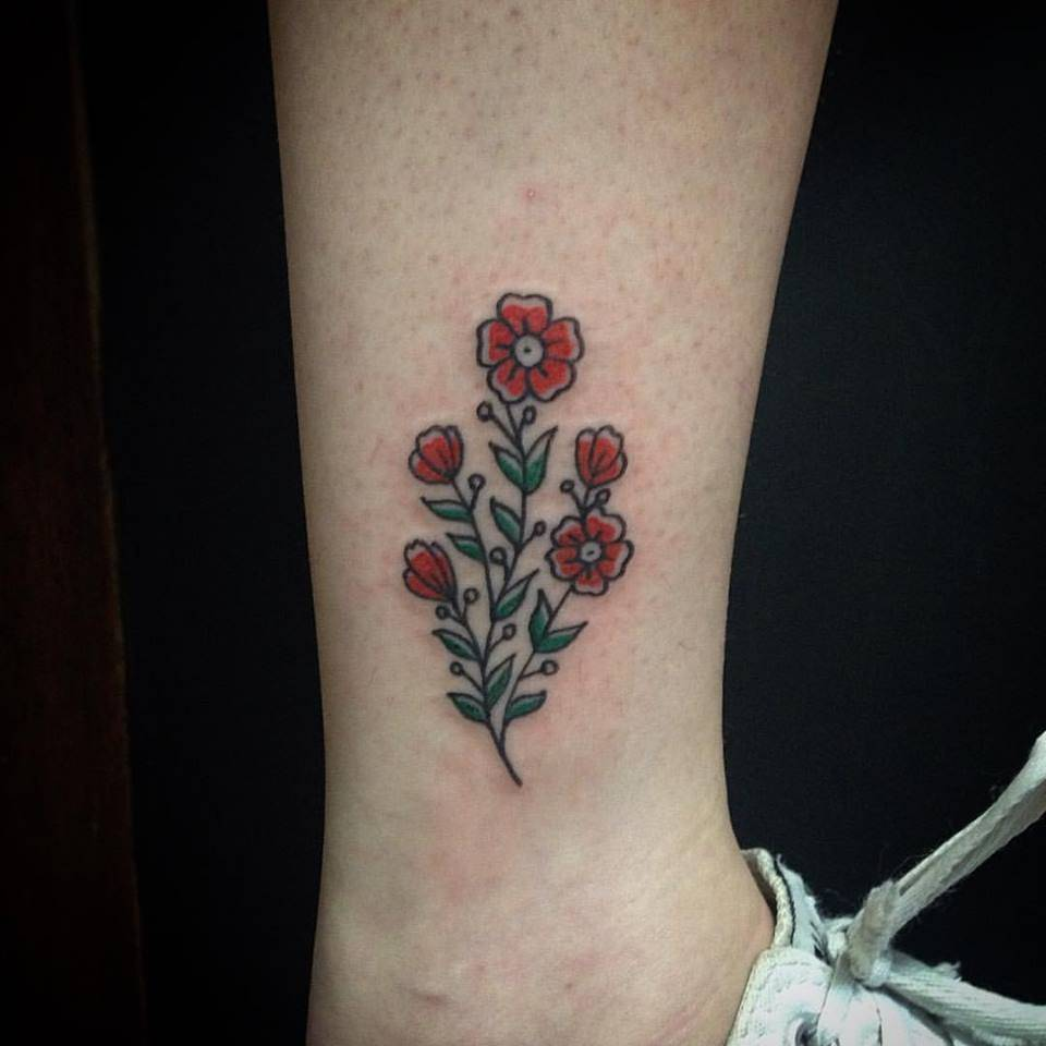 Red and green flower tattoo on ankle