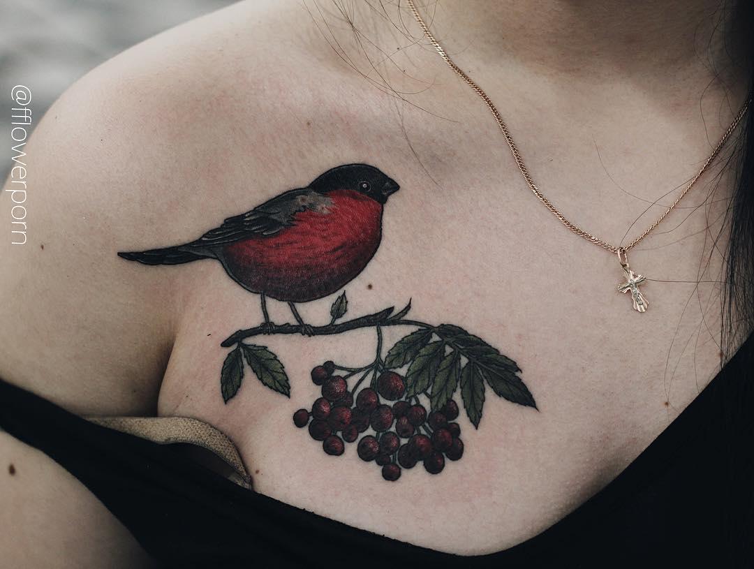 Tattoo of a little bullfinch on a rowan branch