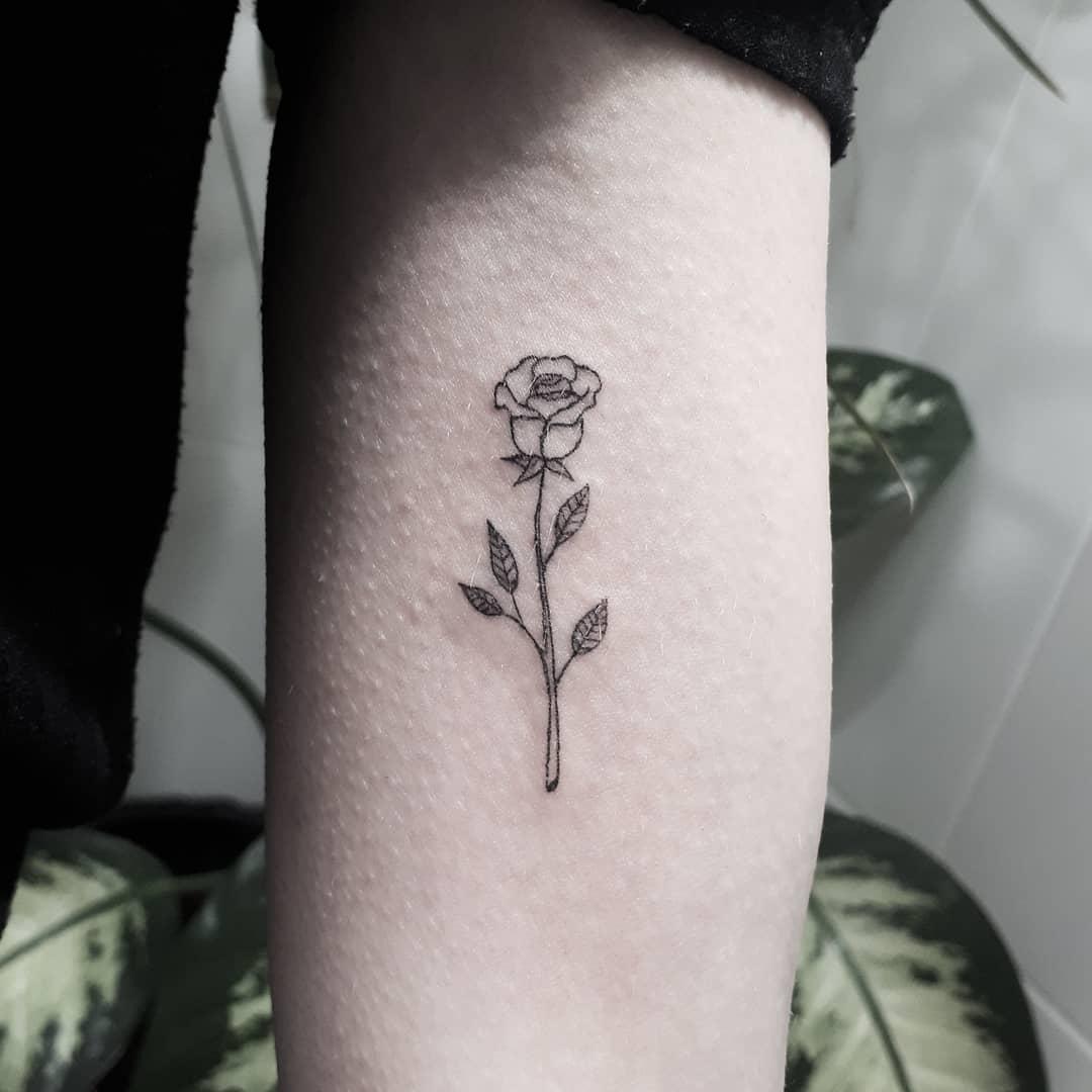 Tiny black rose on the forearm