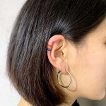 Tiny rainbow tattoo on the right ear