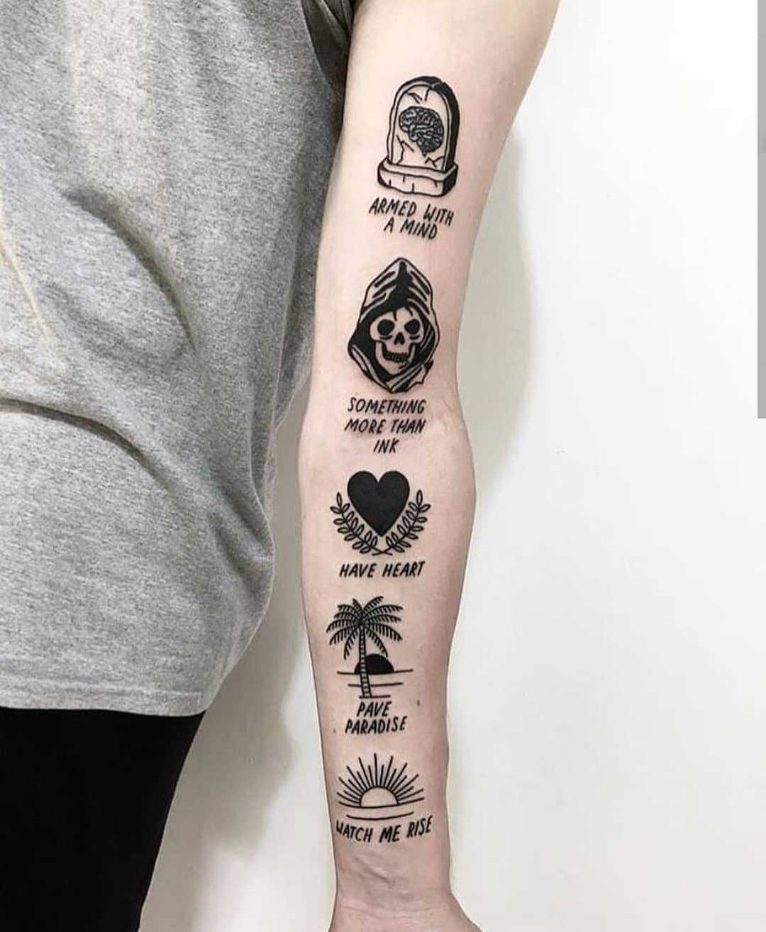 Various black tattoos on the left arm