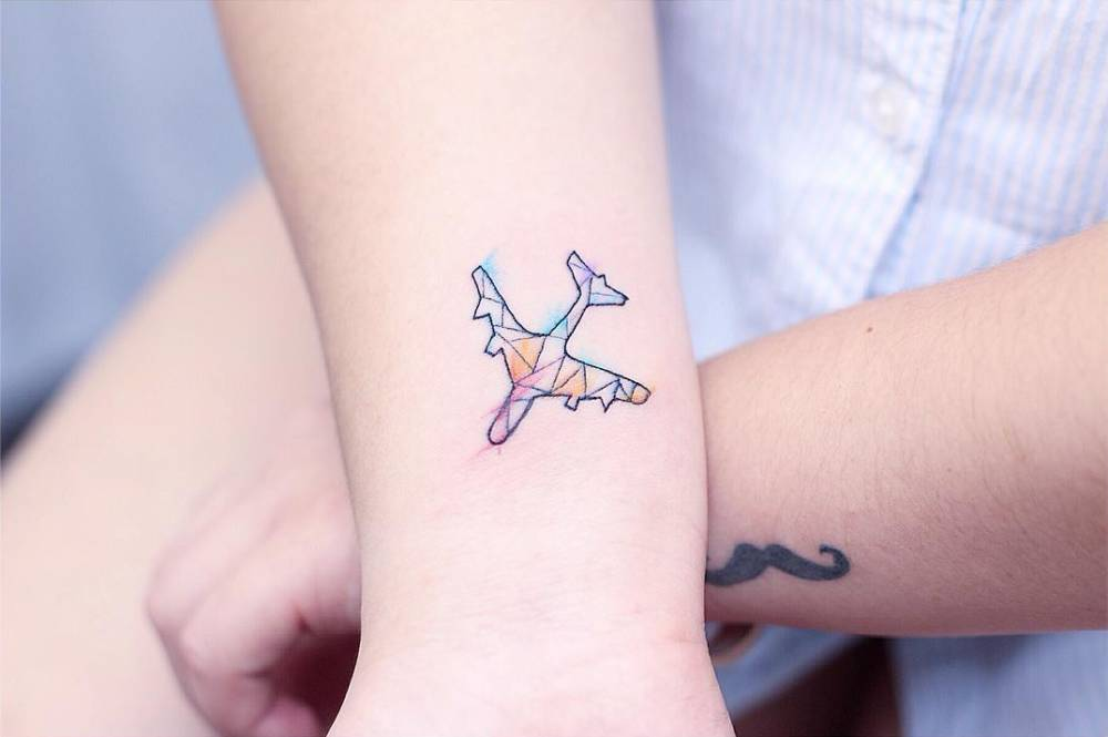 Watercolor airplane tattoo on the wrist