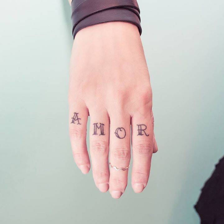 AMOR tattoo on the fingers