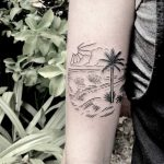 Beach scene tattoo on the forearm