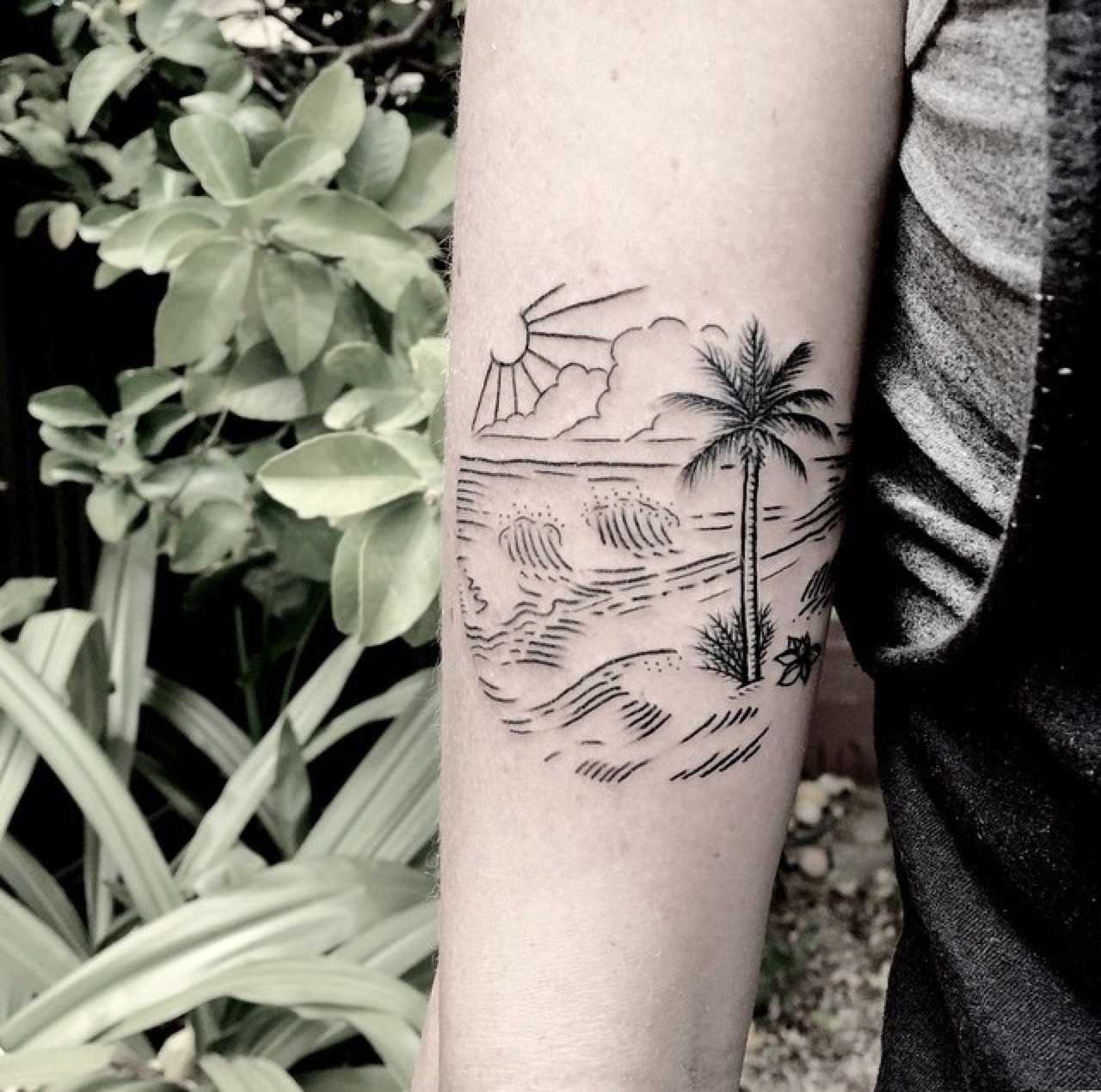 Beach scene tattoo on the forearm