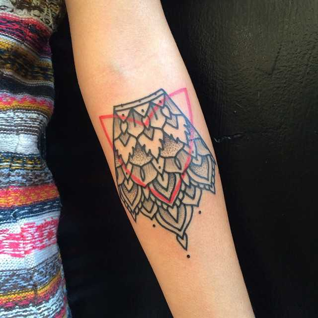 Black and red ornament tattoo on the forearm