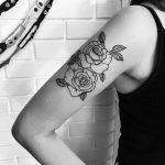 Black and white roses on the bicep