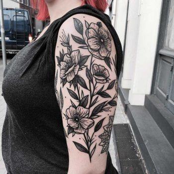 Black flowers tattooed on the arm
