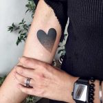 Black gradient heart tattoo on the arm
