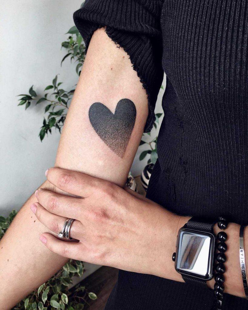 Black gradient heart tattoo on the arm