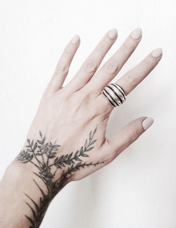 Black greenery inked on the hand